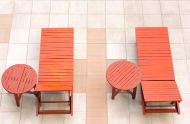 Poolside deckchairs alongside blue swimming pool from top view
