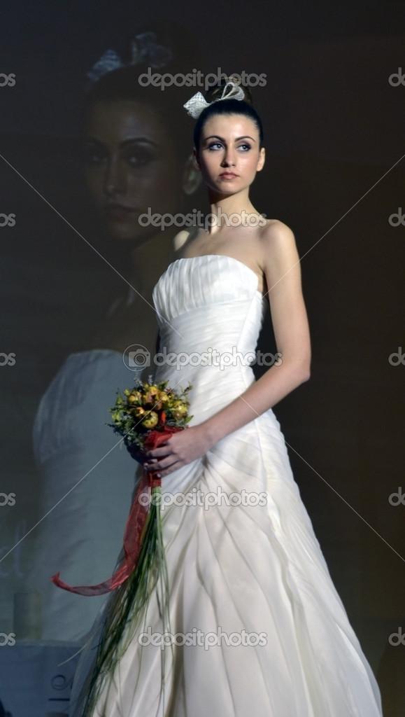 modelo con vestido de novia y ramo de flores entra la pasarela de la
