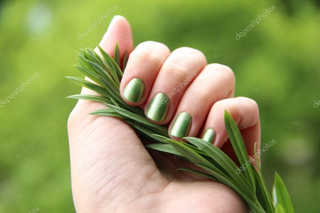 una mano femenina con esmalte de uñas primavera verde sobre la ...