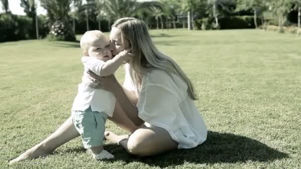 Baby funning s matkou na trávě v parku