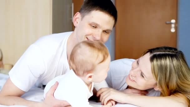 Happy family: father, mother and baby playful in the bedroom
