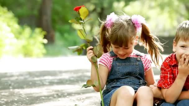 dvě děti mluvit a chlapec prezentovat květ