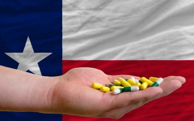 holding pills in hand in front of texas us state flag