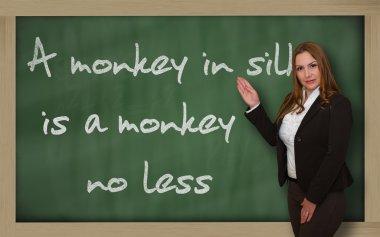 Teacher showing A monkey in silk is a monkey no less on blackboa
