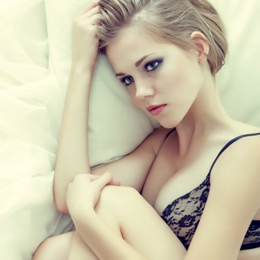Fashion portrait of a sensual girl in white bed