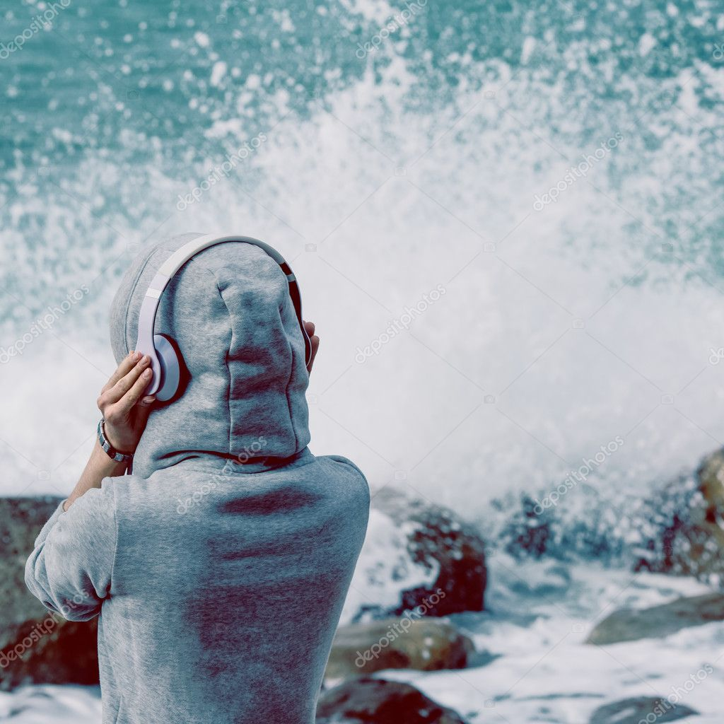 girl listening to music on the shore