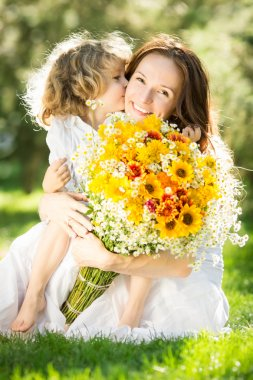 Woman and child holding bouquet of flowers