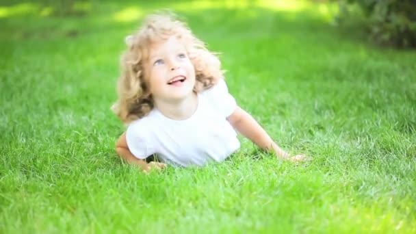 šťastné dítě hraje na zelené trávě na jaře parku. koncept zdravého životního stylu
