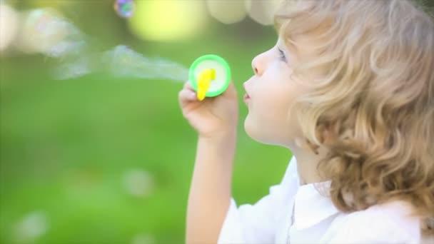 bambino felice soffiando bolle di sapone nel parco di primavera. rallentatore