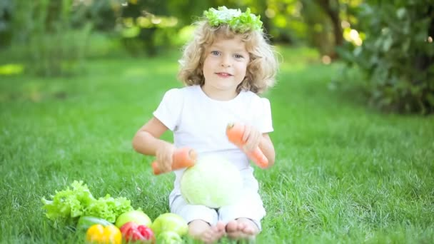 happy child playing with fruits and vegetables in spring park. healthy eating concept