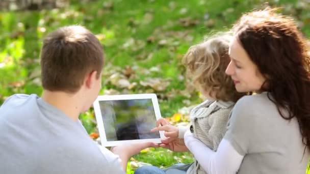 rodina tři sledují snímky na kartě v parku