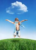Fotografie glückliches Kind, das im Freien springt