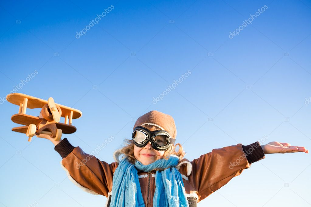 Happy kid playing with toy airplane against blue sky