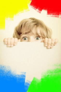 Child looking from behind the paper blank