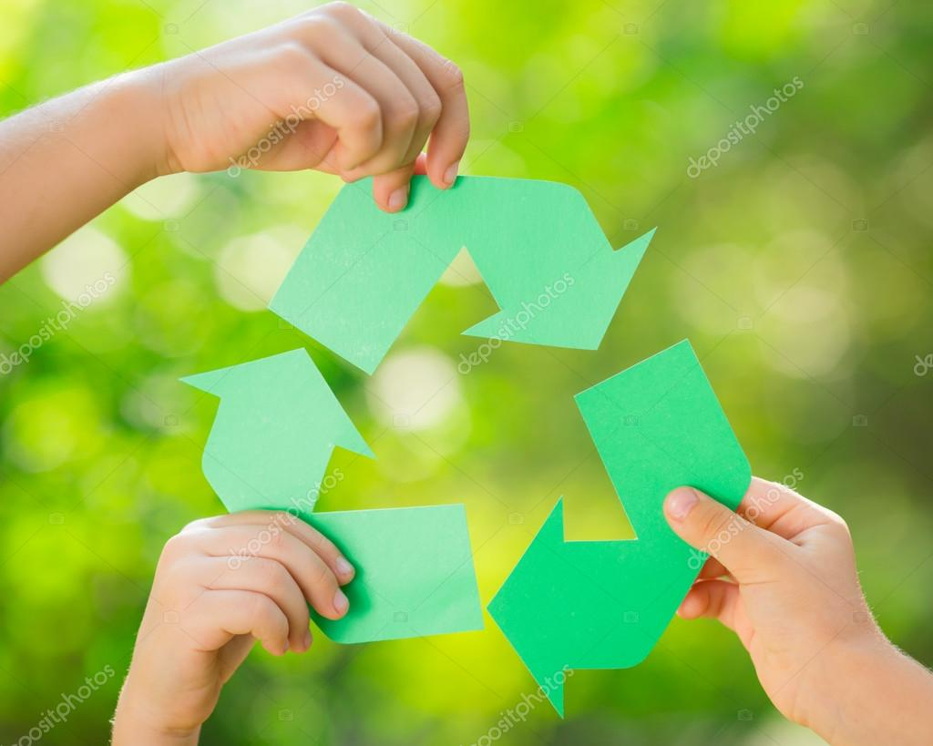 Paper RECYCLE sign in childrens hands