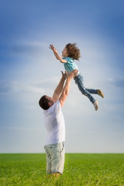 Happy father playing with kid in green spring field against blue sky stock vector