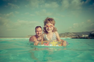 Happy child with father in swimming pool