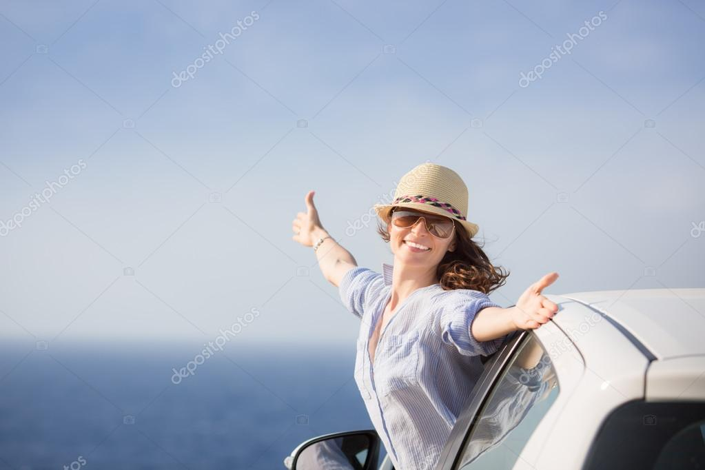 Happy woman driver at the beach
