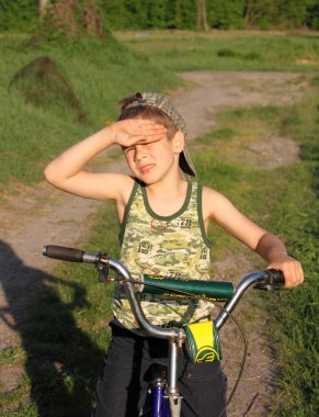 A boy on a bicycle squinting from the sun