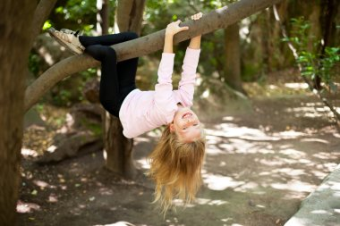 Girl hangs from a tree
