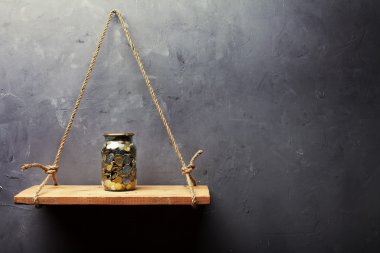 Glass jar with coins on the old wood shelf