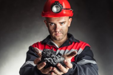 Coal miner holding lump of coal