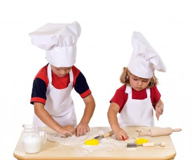 Children making cookies dressed as chefs