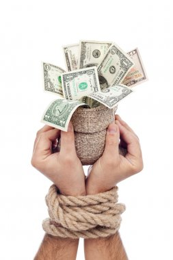 Prisoner of profit - man holding bag of money