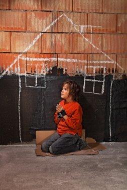 Poor homeless beggar boy praying for a shelter concept
