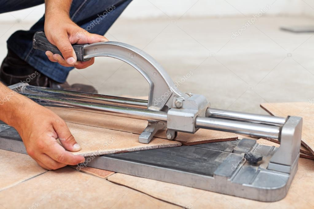 Mattonelle di pavimento operaio taglio con taglierina manuale