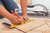 Fektetése kerámia padlólapok - ember kezét Vértes