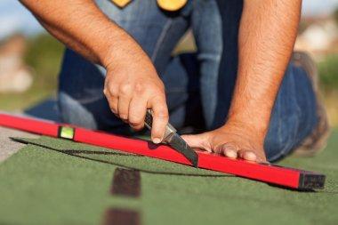 Worker installing bitumen roof shingles