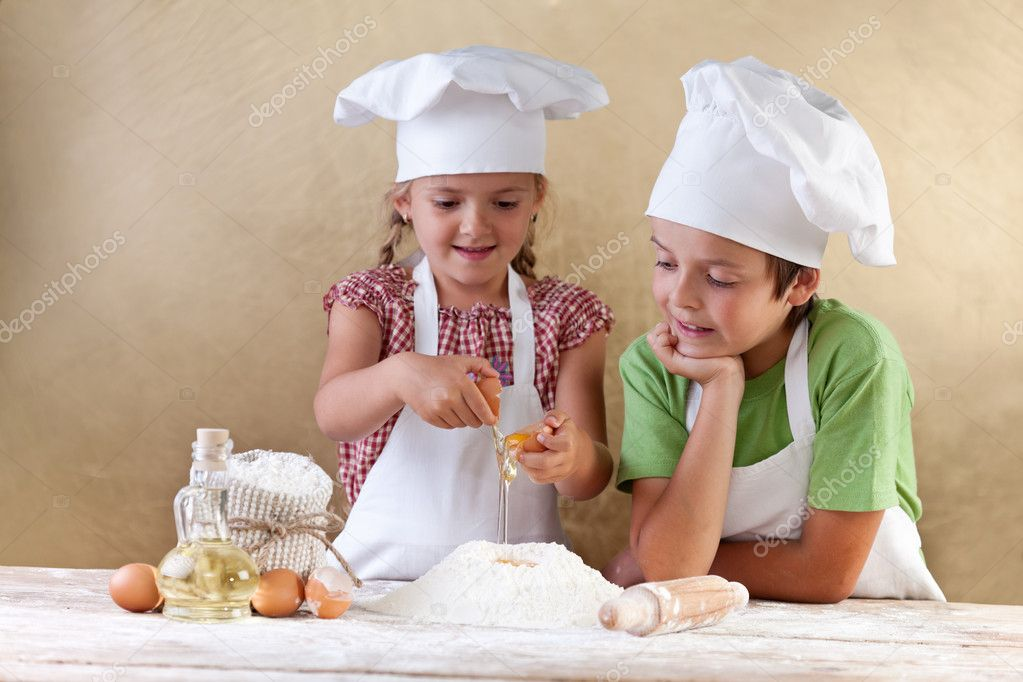Kids with chef hats preparing the cake dough