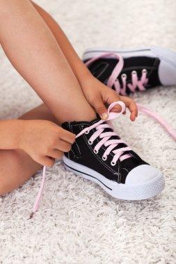 Child hands tie shoelaces
