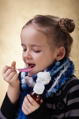 Young girl taking cough medicine