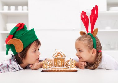Kids with funny christmas hats and gingerbread house
