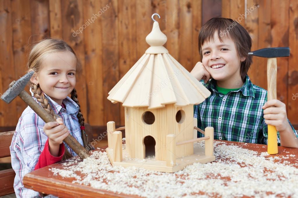 Happy kids building a bird house