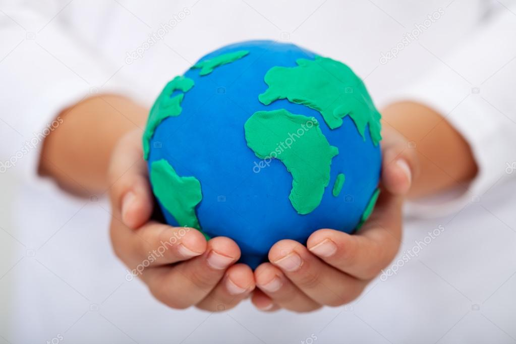 Our home - child holding earth made of clay