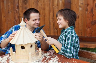 Father and son building a bird house together