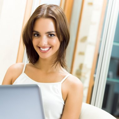 Cheerfull smiling woman working with laptop