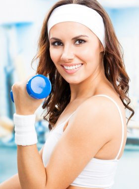 Cheerful woman in fitness wear exercising with dumbbell, at fitness center or gym stock vector