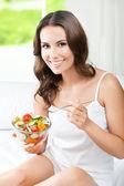 Fotografie Woman eating salad, indoors