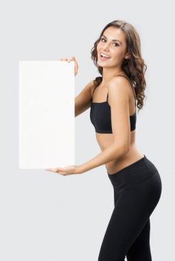 Woman in fitnesswear showing signboard, over grey