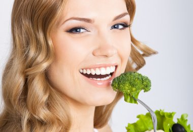 Woman eating broccoli, over gray