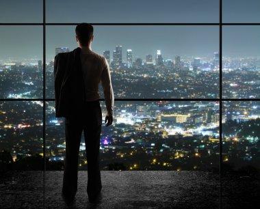 Businessman looks in night city stock vector