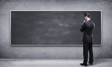 man looking at blackboard
