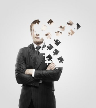 Businessman built of puzzle on white background stock vector
