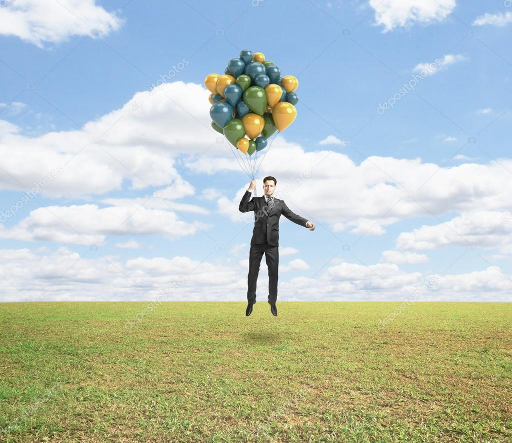 man flying with air baloons