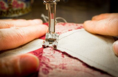 woman at a sewing machine - two hands