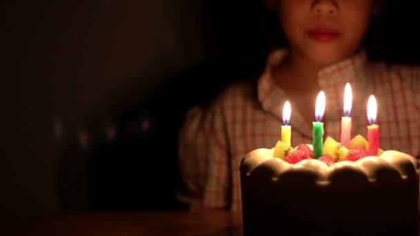 Asijská dívka foukání narozeninový dort svíčky